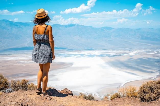 Eine junge frau im kleid auf dem schönen blickwinkel von dantes blick in death valley, kalifornien. vereinigte staaten
