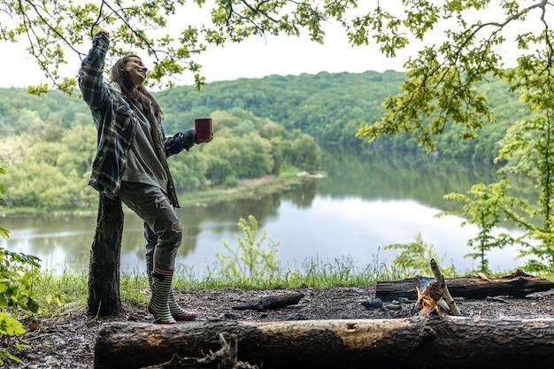 Eine junge frau im wald am fluss wärmt sich am feuer auf und trinkt ein heißes getränk