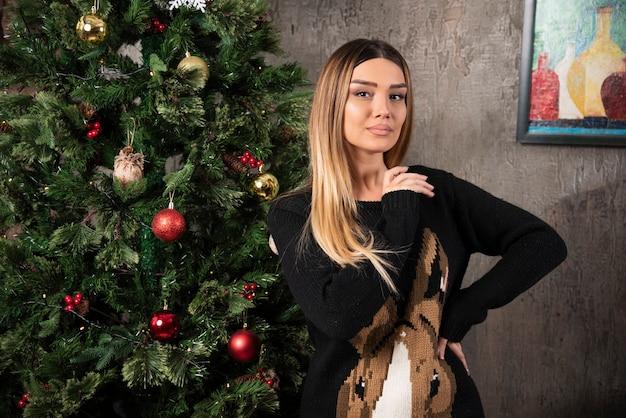 Eine junge frau im warmen pullover, der nahe weihnachtsbaum aufwirft. hochwertiges foto
