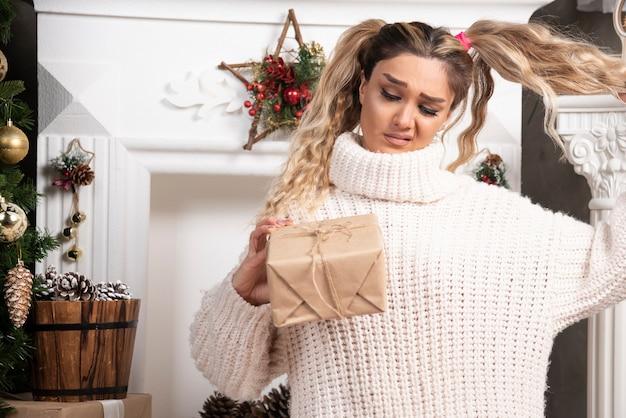 Eine junge frau im weißen pullover zeigt zwei schachteln mit weihnachtsgeschenken.