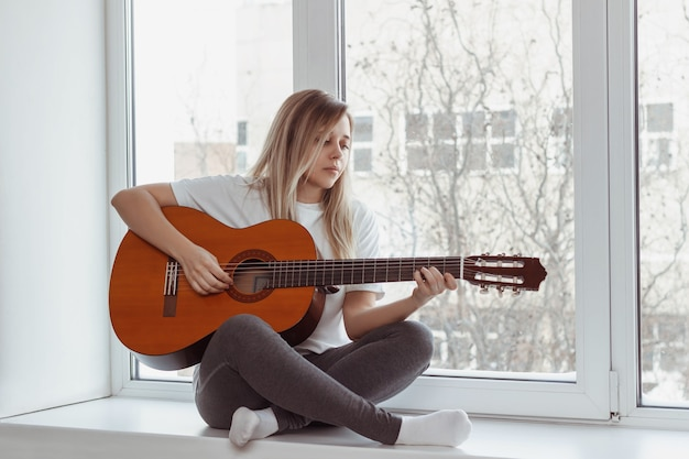 Eine junge frau im weißen t-shirt und in den grauen leggings sitzt auf der fensterbank und spielt akustikgitarre.