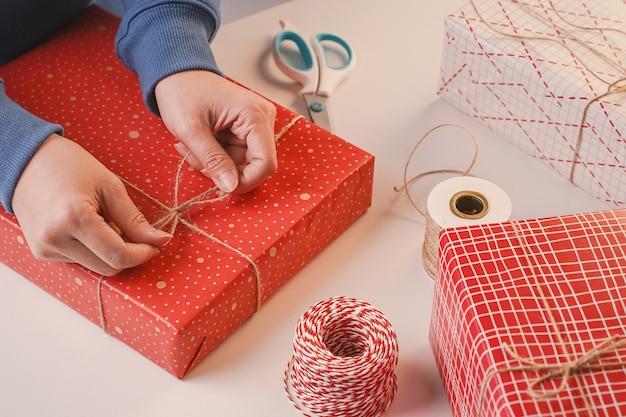 Eine junge frau in blau verpackt, verpackt weihnachtsgeschenk für kinder kinder durch schöne, rote, weiße verpackung mit glitzernden licht, lifestyle.