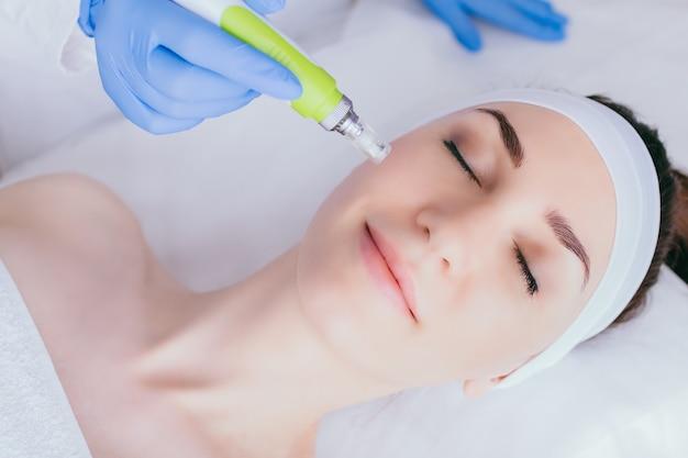 Eine junge frau in der kosmetikpraxis erhält eine fraktionierte mesotherapie für ihr gesicht