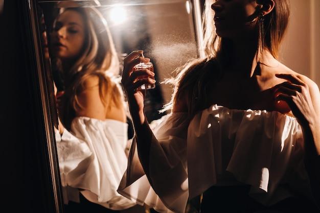 Eine junge frau in einem abendkleid mit parfüm steht vor dem schminktisch zu hause. das mädchen benutzt parfüm, bevor es zu einer party geht.