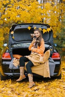 Eine junge frau in einem auto auf dem kofferraum vor dem hintergrund des herbstwaldes sitzt entspannt und umarmt ihren lieblingshund