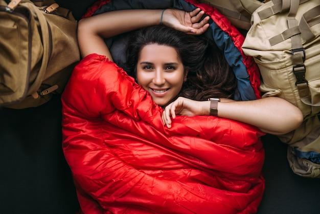 Eine junge frau in einem bequemen schlafsack in einem zelt, draufsicht. ein tourist im schlafsack. ein reisender, eingewickelt in einen roten schlafsack. reisen, campingkonzept, abenteuer. reisen mit zelt