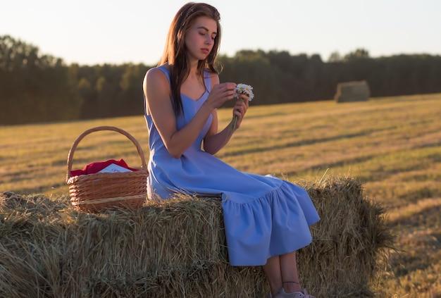 Eine junge frau in einem blauen kleid mit einem strauß gänseblümchen sitzt auf einem heuhaufen auf einem gemähten feld