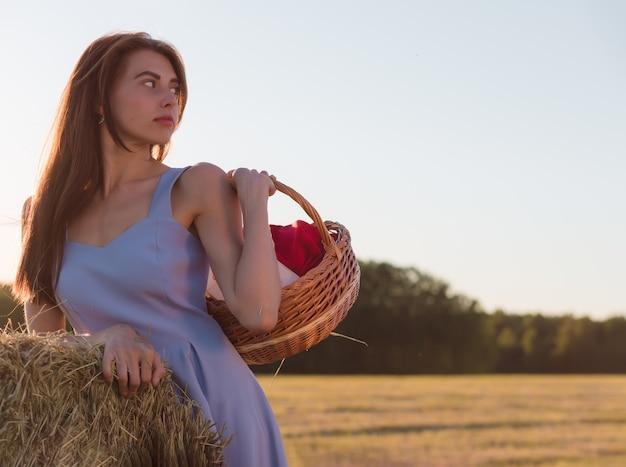 Eine junge frau in einem blauen kleid steht neben einem heuhaufen auf einem gemähten feld