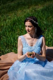 Eine junge frau in einem blauen langen kleid sitzt mit einem sarg in der hand vor einer grünen wiese. modeporträt eines schönen mädchens mit einem lächeln auf ihrem gesicht. verlobungsring-box