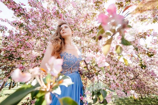 Eine junge frau in einem blauen seidenkleid steht vor dem hintergrund eines rosenbaums in einem apfelgarten
