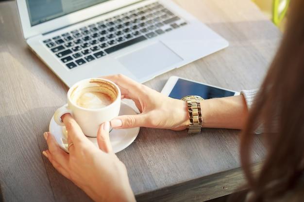 Eine junge frau in einem café hält eine tasse kaffee.