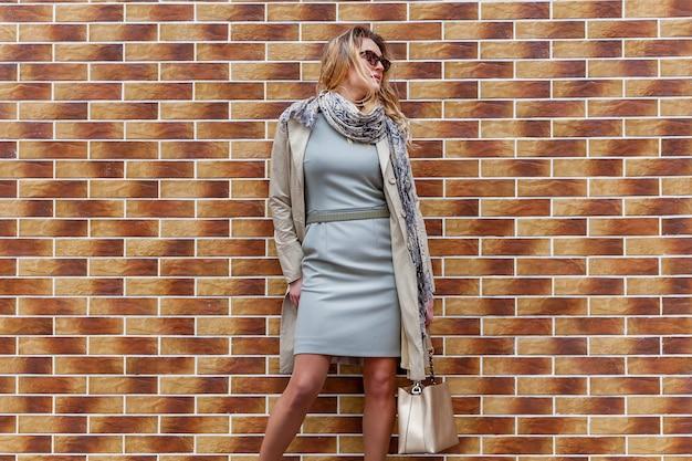 Eine junge frau in einem grauen mantel, einem kurzen kleid und einem schal posiert gegen die backsteinmauer der straße.