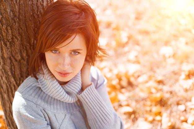 Eine junge frau in einem grauen pullover sitzt allein an einem baum gelehnt an einem schönen tag im park...