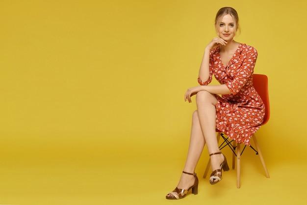 Eine junge frau in einem hellen sommerkleid mit einem blumenmuster, das auf dem stuhl über gelber wand sitzt, lokalisiert