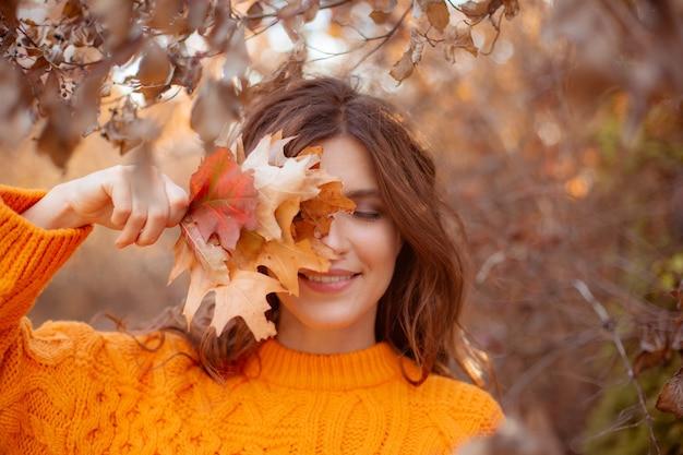 Eine junge frau in einem herbstpark in einem orangefarbenen pullover