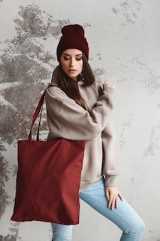 Eine junge frau in einem hoodie mit einer großen einkaufstasche neben der wand.