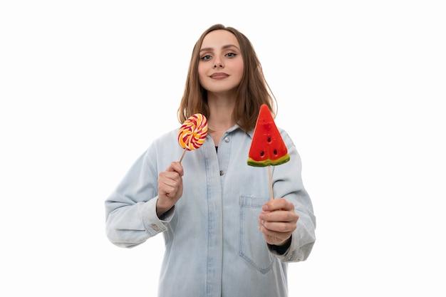 Eine junge frau in einem jeanshemd posiert mit farbigen lutschern