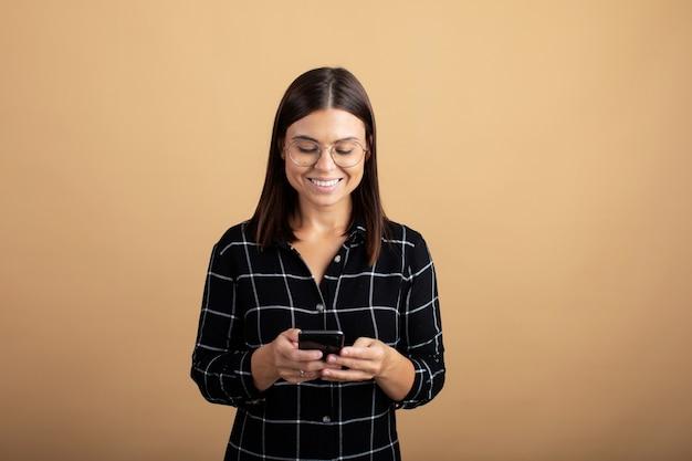 Eine junge frau in einem karierten kleid steht auf einem orangefarbenen hintergrund und spielt mit ihrem telefon