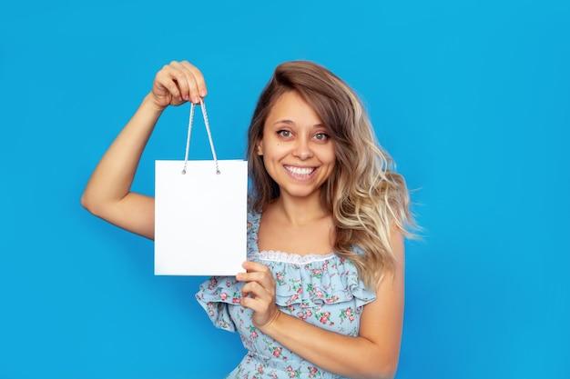 Eine junge frau in einem kleid hält und zeigt eine weiße papiertasche mit leerem platz für ein logo