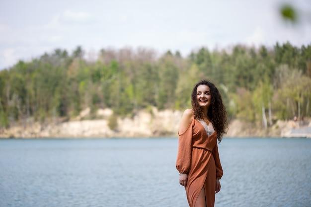 Eine junge frau in einem kleid steht auf einem holzmauerwerk inmitten eines blauen sees. mädchen lächelt glücklich und die sonne scheint, sommertag. sie hat lockiges langes haar und ein europäisches aussehen