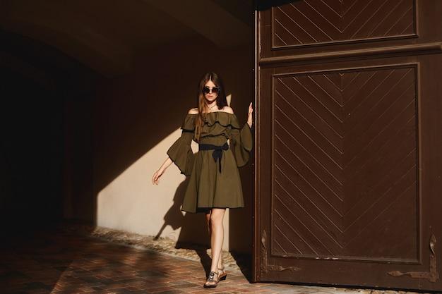 Eine junge frau in einem kleid und einer modischen sonnenbrille, die am sommertag neben der antiken holztür aufwirft