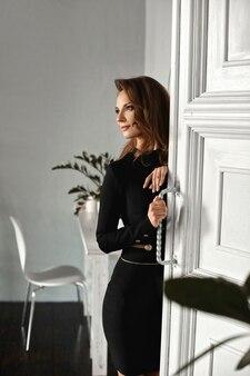 Eine junge frau in einem kurzen schwarzen kleid, das in der nähe einer vintage-tür drinnen aufwirft