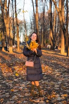 Eine junge frau in einem langen mantel sammelt gelbe blätter im wald leaves