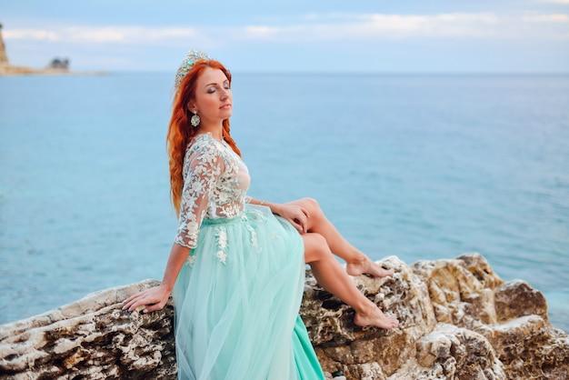 Eine junge frau in einem minzkleid sitzt auf einem großen stein am ufer der adria