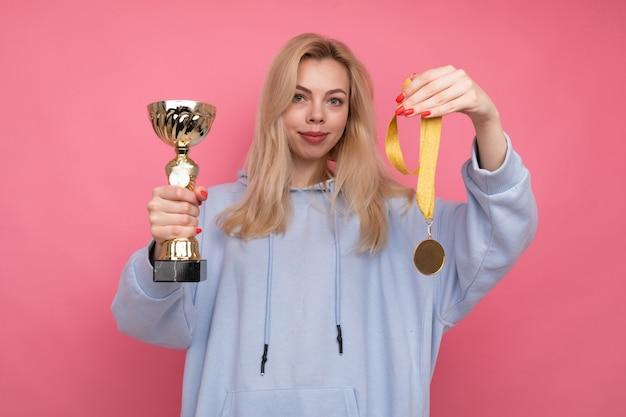 Eine junge frau in einem modischen hoodie hält eine goldene tasse und eine medaille