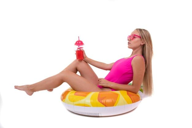 Eine junge frau in einem rosa badeanzug, der auf einem aufblasbaren schwimmkreis liegt und limonade trinkt