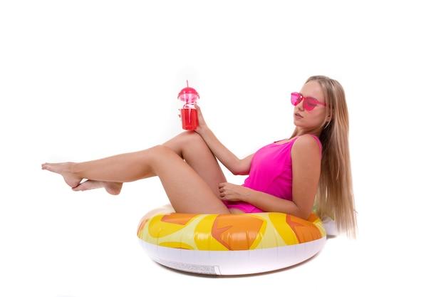 Eine junge frau in einem rosa badeanzug und einer brille liegt auf einem aufblasbaren schwimmkreis und trinkt limonade