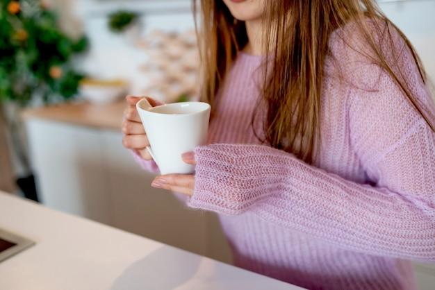 Eine junge frau in einem rosa pullover hält die kaffeetasse in nahaufnahme