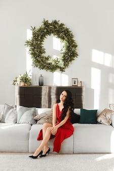 Eine junge frau in einem roten abendkleid über dem wohnzimmerinnenraum, der für weihnachten verziert wird