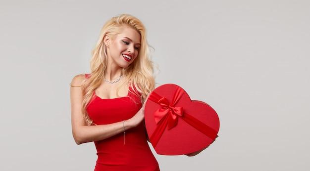 Eine junge frau in einem roten kleid bläst einen kuss. hält in ihren händen eine herzförmige geschenkbox. valentinstag und 8. märz