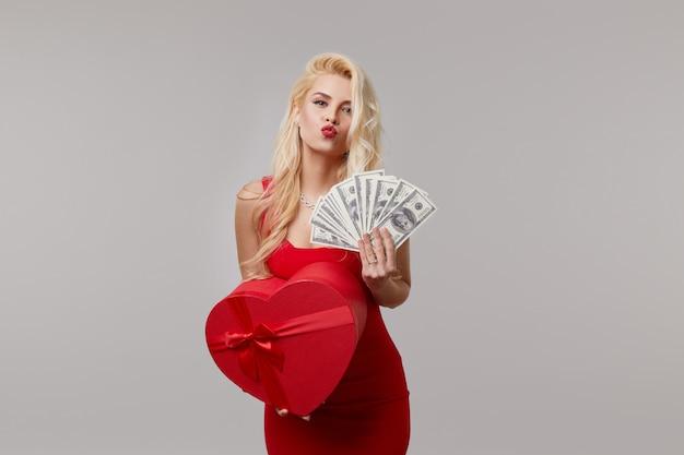Eine junge frau in einem roten kleid hält in ihren händen bargeld, geld, dollar und eine herzförmige geschenkbox. valentinstag und 8. märz