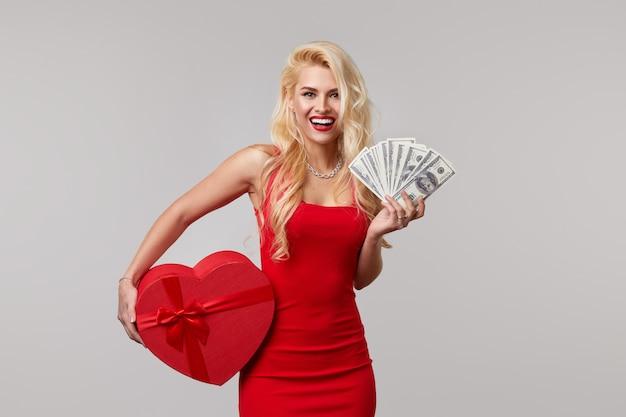 Eine junge frau in einem roten kleid hält in ihren händen bargeld, geld, dollar und eine herzförmige geschenkbox. valentinstag