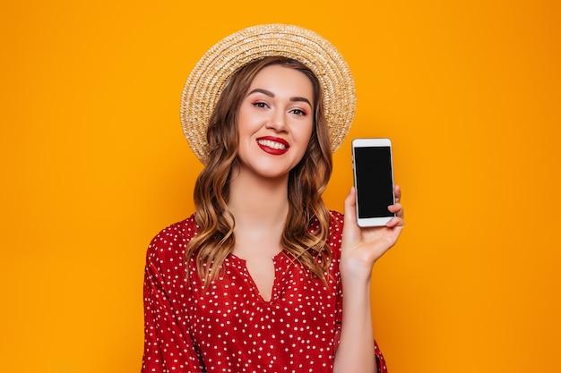 Eine junge frau in einem roten sommerkleidhut hält ein handy und zeigt es der kamera mit leerem schwarzen bildschirmmodellraum für design-online-bestelleinkaufskonzept orange wand