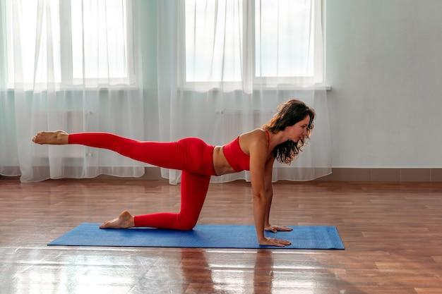 Eine junge frau in einem roten trainingsanzug, der übungen oder yoga im fitnessstudio macht.
