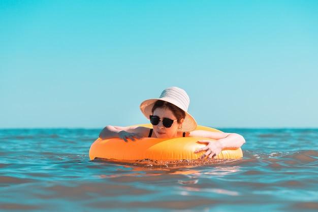 Eine junge frau in einem schwarzen badeanzug und hut lernt, mit einem kreis zu schwimmen.