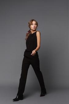 Eine junge frau in einem schwarzen freizeitoutfit, das über den grauen hintergrund geht. modellmädchen in einem schwarzen anzug auf dem grauen hintergrund