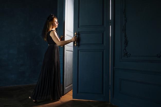 Eine junge frau in einem schwarzen kleid öffnet eine tür, aus der licht strömt