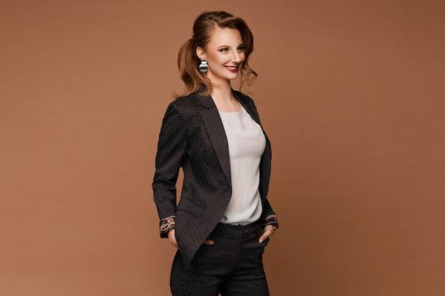 Eine junge frau in einem stilvollen anzug und einer weißen bluse lacht und posiert auf der beigen oberfläche, isoliert mit kopierraum