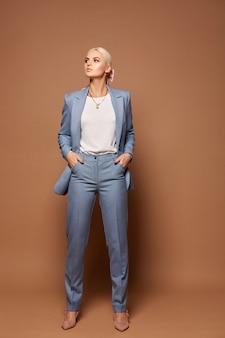 Eine junge frau in einem trendigen blauen anzug, einer weißen bluse und beigen schuhen, die über beigem hintergrund mit kopienraum aufwerfen. konzept der geschäftsmode und schönheit