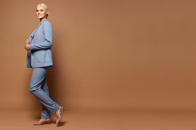 Eine junge frau in einem trendigen blauen anzug und beige schuhen, die über beigem hintergrund aufwerfen, lokalisiert mit kopienraum