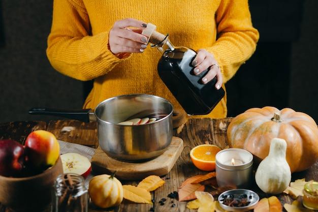 Eine junge frau in einem warmen, gestrickten, gelben pullover gießt wein aus einer glasflasche in eine pfanne, um heißen glühwein herzustellen