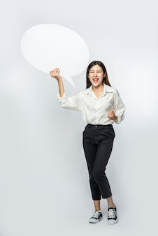 Eine junge frau in einem weißen hemd, das ein gedankenkastensymbol hält