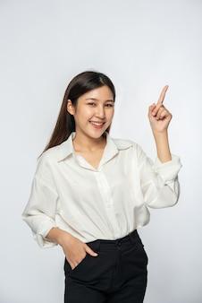 Eine junge frau in einem weißen hemd und zeigt nach oben
