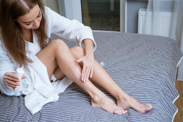 Eine junge frau in einem weißen kittel befeuchtet ihre beine mit sahne. körperpflegekonzept.