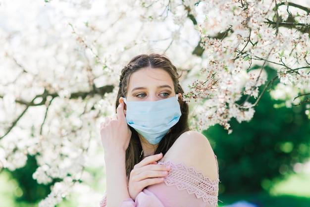 Eine junge frau in einer medizinischen gesichtsmaske, um die ausbreitung des coronavirus im park zwischen blühenden bäumen zu vermeiden.