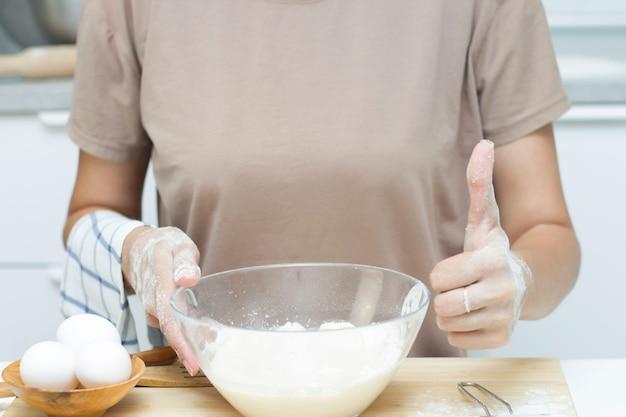 Eine junge frau in einer modernen küche hält eine tasse mehl und zeigt ihren daumen